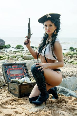 mujer desnuda sentada: Hermosa mujer pirata que se sienta cerca cofre del tesoro en la playa con una pistola en la mano cl�sica