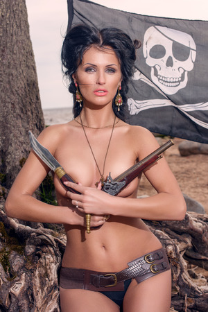 topless brunette: Topless pirate woman covers her breasts with a classic pistols