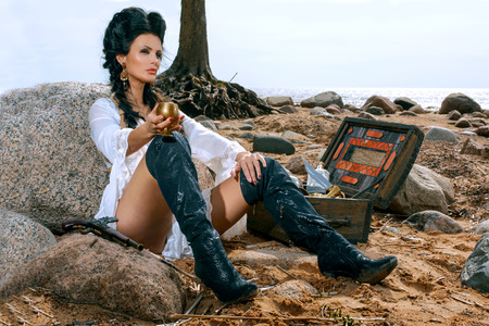 woman nude standing: Beautiful pirate woman sitting near treasure chest on the beach with a golden goblet in her hand Stock Photo