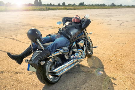 laying forward: Biker in leather jacket resting on a motorcycle.