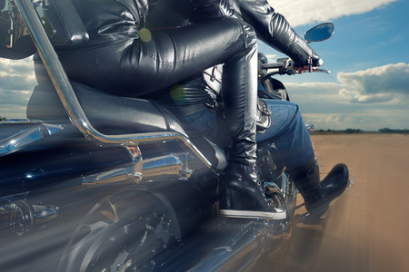 Biker Man and woman wearing black leather jackets riding on motorcycle Stock Photo