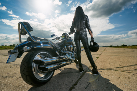 Biker girl in leather jacket standing by a motorcycle. Rear view Banco de Imagens
