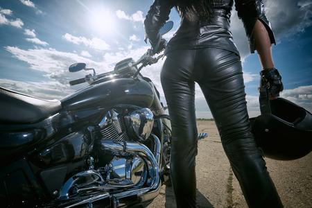 chaqueta: Muchacha del motorista en la chaqueta de cuero de pie junto a una motocicleta. Vista trasera Foto de archivo