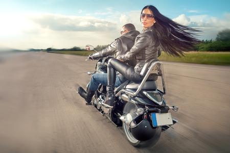 jinete: Biker Hombre y mujer vistiendo chaquetas de cuero negro y gafas de sol con estilo que montan en motocicleta Foto de archivo
