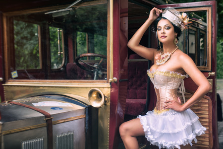 fashion art: Portrait of a sexy beautiful woman posing over retro car. Cabaret and pin-up concept.