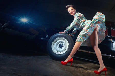 Beautiful elegant woman change the wheel of car in pin up style