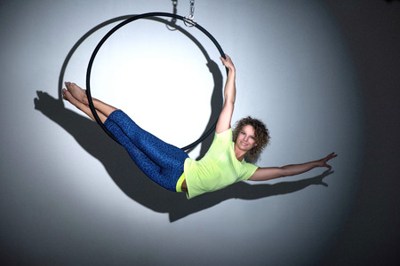 Woman doing entertainment exercise with aerial hoop midair in spotlight