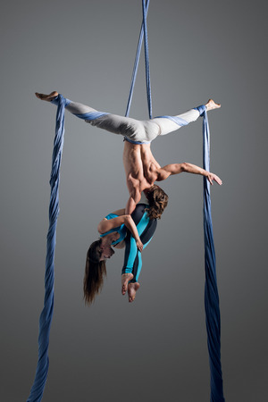 Sporty couple doing exercise with elastics, aerial silk. Sport training gym and lifestyle concept. Anti-gravity yoga.