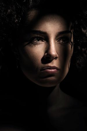 Jonge mooie vrouw in een donkere schaduw en licht Stockfoto