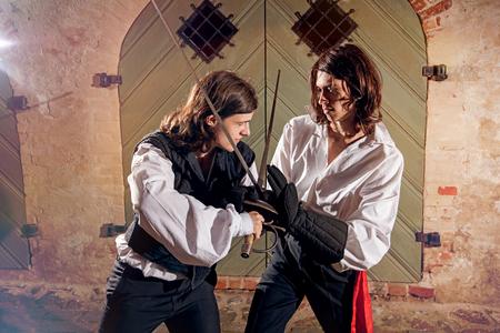 pelea: Los hombres que luchan con espadas en la antigua calle de la ciudad Foto de archivo