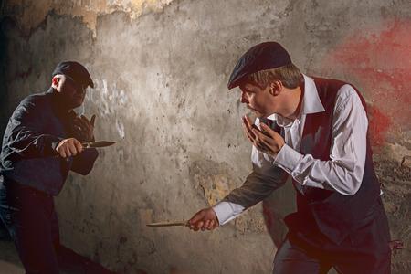 pelea: Los hombres que luchan con cuchillos en la calle urbana