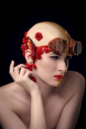 bald girl: Bald girl with a art make up and steampunk glasses, on the one hand a mechanical robot, on the other blooming desert