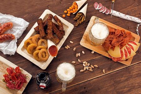 wooden table top view: Mugs of beer with snacks on wooden table, top view