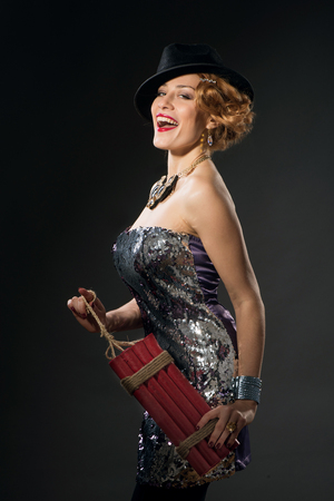 the caucasian beauty: Beautiful woman in vintage style dress and hat holding dynamite on dark studio background
