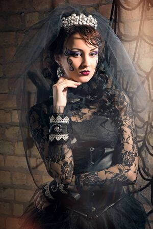 vogue style: Portrait of beautiful young brunette girl in black dress and veil in the Gothic style