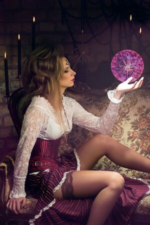 modelo desnuda: bruja atractiva joven con la esfera m�gica vestido con traje de �poca