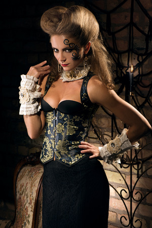 the caucasian beauty: sexy young woman wearing corset dress  posing in vintage studio