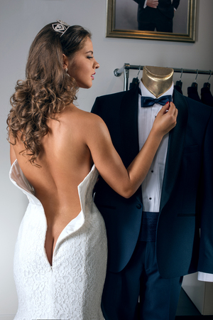 Half naked bride  in wedding dress looks at the grooms suit in the salon