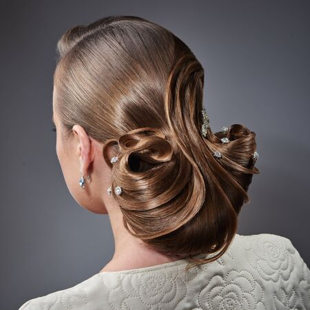 young style: Young beautiful woman with fashion evening hairstyle posing in the studio