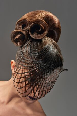 vogue style: Young beautiful woman with fashion evening hairstyle posing in the studio