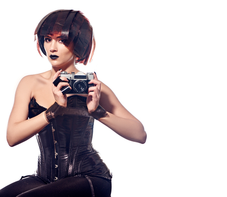 bodice: Beautiful stylish woman in leather corset with film Hairstyle holding retro camera and hands tying with filmstrip roll isololated on white background
