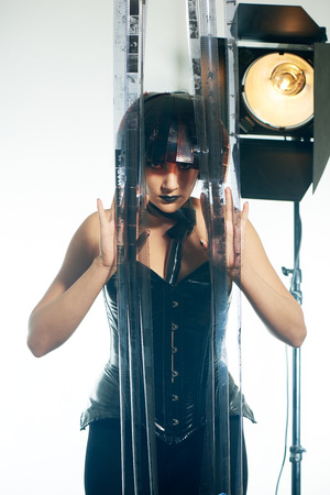 filmstrip: Beautiful stylish woman with film hairstyle in leather corset posing in studio with filmstrip rolls Stock Photo