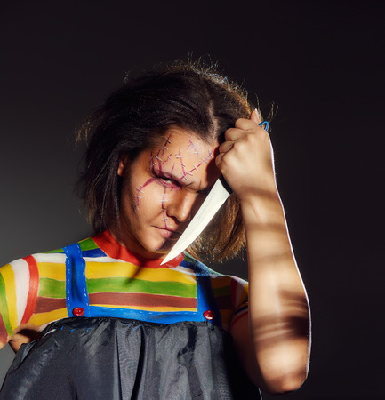 scars: Close-up image of an upset woman holding knife near face with scars and stitches Stock Photo