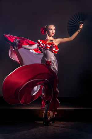 Beautiful Woman traditional Spanish Flamenco dancer dancing in a red dress with black fan Stock Photo