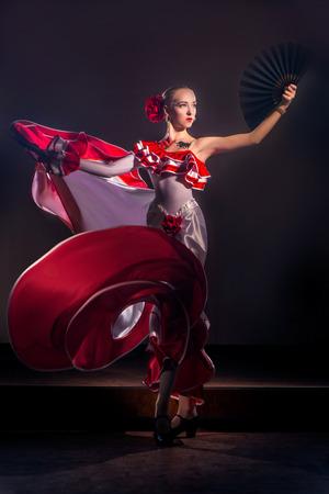 Hermosa mujer tradicional baile del bailarín de flamenco español en un vestido rojo con el ventilador negro Foto de archivo