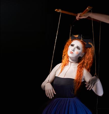 Red-fille aux cheveux stylisé comme marionette marionnettes sur fond noir