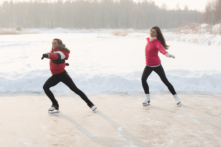 Coach of figure skating with apprentice practise at the frozen lake in the winter Stock Photo