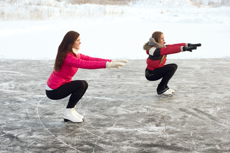 couching: Coach of figure skating with apprentice practise at the frozen lake in the winter Stock Photo