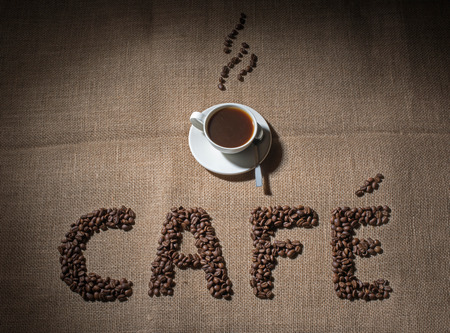 bagging: word cafe of coffee beans and cup of black coffee on bagging background Stock Photo