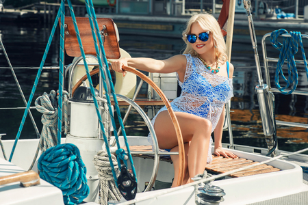 transparent dress: Young beautiful blond woman in white transparent dress and swimsuit standing on yacht at sunny day