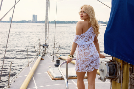 transparent dress: Young beautiful blond woman in white transparent dress standing on yacht at sunny day
