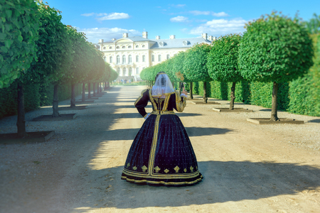 16th century: Historical cosplay. Beautiful woman in the similitude of Marguerite of Navarre, queen of France ancient dress in the garden near palace