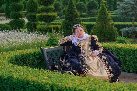 similitude: Historical cosplay. Beautiful woman in the similitude of Marguerite of Navarre, queen of France ancient dress in the garden near palace