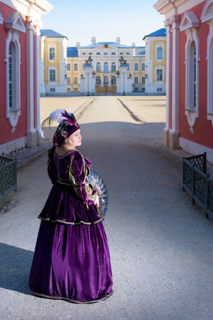 similitude: Historical cosplay. Beautiful woman in the similitude of Isabella dEste Mantua, marquess of Italian ancient dress near palace