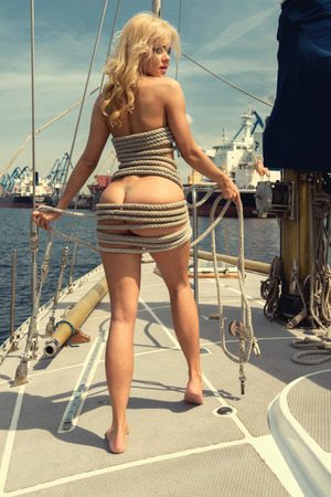 Young beautiful woman tying rope standing on yacht at sunny day
