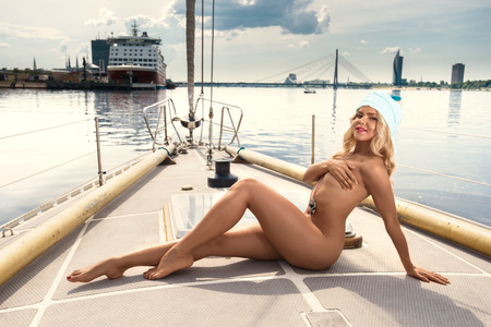 sexy blonde girl: Young beautiful woman standing on yacht at sunny day Stock Photo