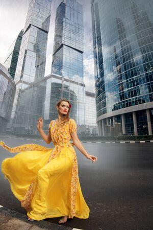 ritratto piena crescita di moda donna in svolazzante abito lungo giallo su sfondo urbano