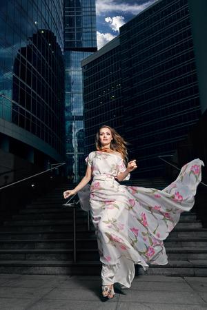 Full growth portrait of fashionable woman in fluttering long dress on urban background Reklamní fotografie