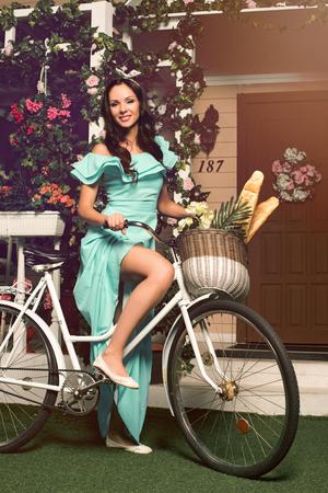 gente adulta: Hermosa mujer joven morena en traje de menta pie con la bicicleta cerca de su casa Foto de archivo