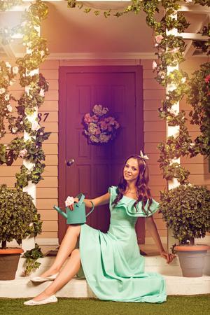 gente adulta: Hermosa mujer joven morena en traje de menta sentado en un porche de su casa Foto de archivo