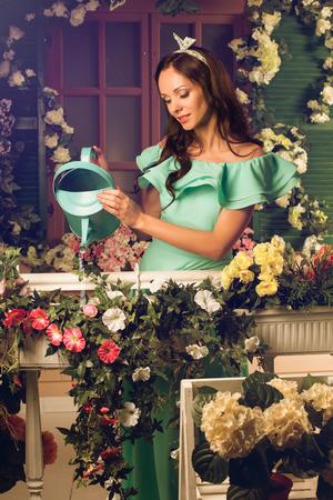 gente adulta: Hermosa mujer joven morena en traje de menta regando flores en un porche de su casa Foto de archivo