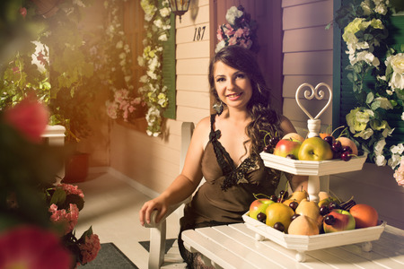backyard woman: Pretty woman sitting at table with fruit vase on it in cozy backyard with rose flowers around