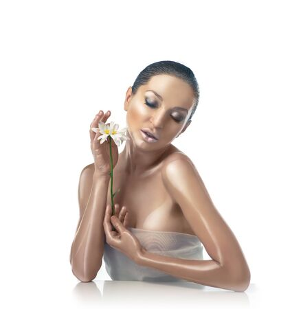 brown skin: beautiful brunette woman with perfect brown skin with chamomile posing on a white background