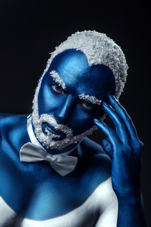 Man painted in blue color with snowy hair and beard on black background Stock Photo