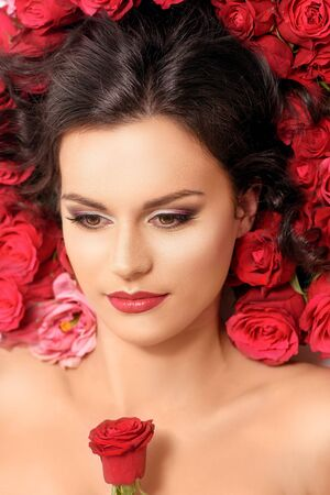 beautiful rose: Portrait of fashionable young model lying in red roses