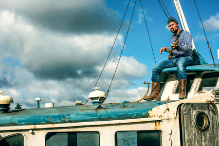 loner: Old salt man playing guitar on his rusted ship
